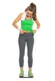 Mulher que verifica a gordura corporal ao estar em escalas Fotos de Stock Royalty Free
