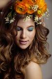 A jovem mulher da beleza com flores e compõe fotografia de stock royalty free