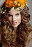 A jovem mulher da beleza com flores e compõe perto Fotos de Stock Royalty Free