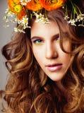 A jovem mulher da beleza com flores e compõe perto acima, sprin real Imagem de Stock