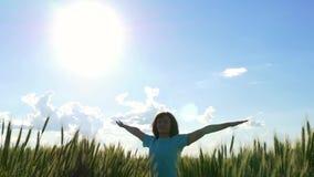 A jovem mulher da beleza está girando suas mãos ao lado em um campo do trigo verde sobre um céu nebuloso filme