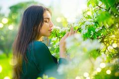 Jovem mulher da beleza que aprecia a natureza no pomar de maçã da mola, menina bonita feliz em um jardim com as árvores de fruto  imagens de stock royalty free