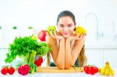 Jovem mulher da beleza que guarda legumes frescos e frutos em sua cozinha em casa Fotos de Stock Royalty Free