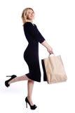 Jovem mulher da compra que mantém sacos isolados no fundo branco do estúdio Forma e vendas do amor Menina loura feliz no gl luxuo fotografia de stock