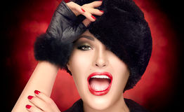 Jovem mulher da forma do inverno no chapéu forrado a pele que gesticula e que faz caretas Fotos de Stock