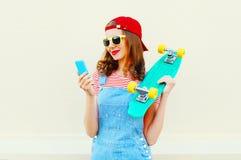 A jovem mulher da forma está usando o smartphone e guarda o skate sobre o branco fotos de stock