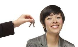Jovem mulher da raça misturada que está sendo entregada chaves no branco Foto de Stock