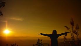 A jovem mulher da silhueta do por do sol que sente à liberdade e relaxa Fotos de Stock