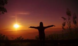 A jovem mulher da silhueta do por do sol que sente à liberdade e relaxa Fotografia de Stock Royalty Free