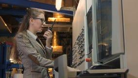 A jovem mulher da vista lateral está e fala no painel de controle video estoque