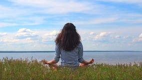 Jovem mulher da vista traseira em roupa listrada que senta-se na pose dos lótus na praia do rio Sentimento caucasiano da mulher filme