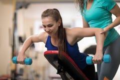 Jovem mulher de ajuda do instrutor pessoal com equipamento de treino do peso no gym imagem de stock royalty free