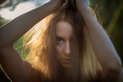 A jovem mulher de cabelo escuro está com olhos grandes e olhar de exigência em uma árvore de salgueiro velha com ombros finos fotografia de stock