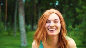 Jovem mulher de cabelo vermelha smeary com pó colorido após Holi que ri da câmera filme