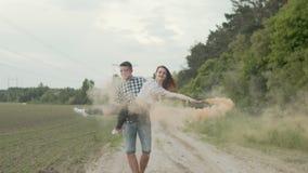 Jovem mulher de circundamento masculina com a bomba de fumo exterior video estoque
