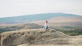 A jovem mulher de encantamento com cabelo louro senta-se apenas sobre a montanha em Geórgia na roupa fraca, meditação da manhã de vídeos de arquivo