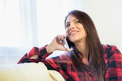 Jovem mulher de encantamento que aprecia uma conversação em seu telefone celular ao sentar-se no sofá em casa fotografia de stock