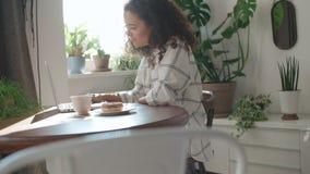 Jovem mulher de encantamento que datilografa no laptop em casa filme