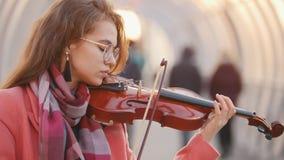 Jovem mulher de encantamento que joga o violino para livre em público video estoque