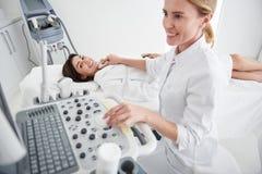 Jovem mulher de encantamento que tem o ultrassom do tiroide no centro do bem-estar imagem de stock royalty free