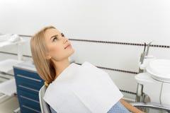 Jovem mulher de espera que encontra-se na sala do dentista Fotografia de Stock Royalty Free