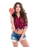A jovem mulher de fascínio bonita que está e que guarda o coração deu forma ao pirulito fotografia de stock