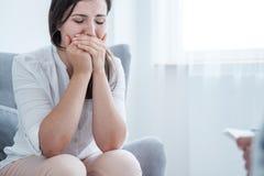 Jovem mulher de grito que cobre sua boca com as mãos ao sentar-se em uma sala brilhante Espaço vazio no fundo imagem de stock