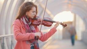 Jovem mulher de Insipired que joga o violino na passagem aérea filme