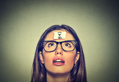 A jovem mulher de pensamento com areia cronometra a etiqueta do sinal em sua testa Foto de Stock
