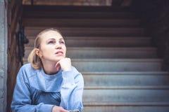 A jovem mulher de pensamento que senta-se em escadas e olha acima com espaço da cópia Conceito para a previsão e a maneira para a Fotografia de Stock