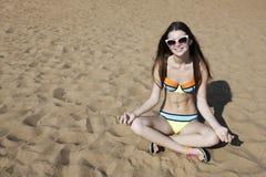 A jovem mulher de relaxamento na praia em Lotus levanta Foto de Stock
