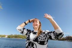 A jovem mulher de riso olha na distância e acena Imagem de Stock