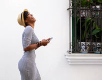 Jovem mulher de riso que anda com telefone celular Imagem de Stock