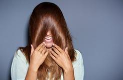 Jovem mulher de riso que cobre seus olhos Imagens de Stock