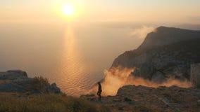 Jovem mulher de Silhuette observando um por do sol dramático bonito acima de um mar de uma montanha alta em Crimeia filme
