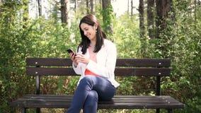 Jovem mulher de sorriso atrativa com o smartphone no parque Deslize o slider vídeos de arquivo