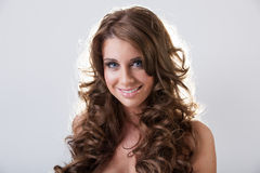 Jovem mulher de sorriso bonita com cabelo encaracolado longo fotografia de stock