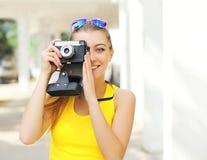 Jovem mulher de sorriso bonita feliz com a câmera retro do vintage imagem de stock royalty free