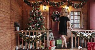 Jovem mulher de sorriso bonita na camiseta preta no fundo das decorações do Natal video estoque