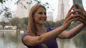 Jovem mulher de sorriso bonita que anda em um parque Usando seu smartphone, fazendo o selfie filme