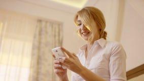 Jovem mulher de sorriso bonita que guarda e que olha o telefone esperto video estoque