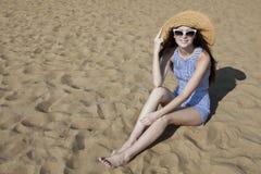 Jovem mulher de sorriso bonita que senta-se na praia Fotos de Stock Royalty Free