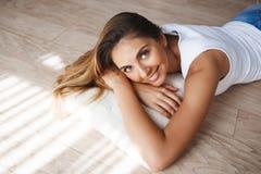 A jovem mulher de sorriso bonita vestiu-se no short branco da camisa e da sarja de Nimes que encontra-se no assoalho fotografia de stock