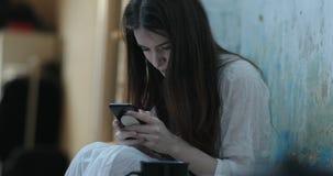 A jovem mulher de sorriso com cabelo escuro longo lê algo em seu smartphone que senta-se no assoalho em uma sala vídeos de arquivo