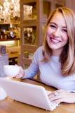 Jovem mulher de sorriso com computador fotografia de stock