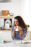 Jovem mulher de sorriso com copo e portátil de café dentro Imagens de Stock