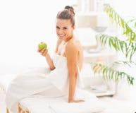 Jovem mulher de sorriso com a maçã que senta-se na tabela da massagem Imagem de Stock Royalty Free