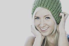 Jovem mulher de sorriso com o beanie feito malha home Imagens de Stock