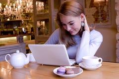 Jovem mulher de sorriso com o computador no breacfast Imagem de Stock Royalty Free