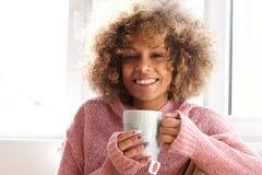 Jovem mulher de sorriso com o copo do chá fotografia de stock royalty free